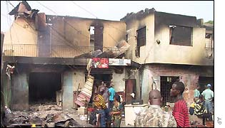 People gather around a destroyed building in Lagos