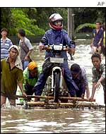 Indonesian youths help a motorist to cross a flooded street with a makeshift raft in Jakarta, 30 January 2002