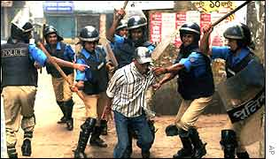 Police beat a protester in Dhaka