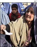 Afghan woman pleads with aid workers for food