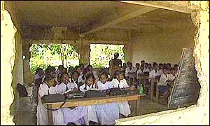 Children sit in classroom by gaping hole