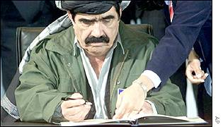 The Governor of Paktia province, Pasha Khan Zadran, signs a document during the UN-sponsored talks on Afghanistan in Bonn in December 2001