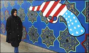 Iranian woman passes by a mural showing a gun painted with the US flag on the wall of the former US embassy in Tehran