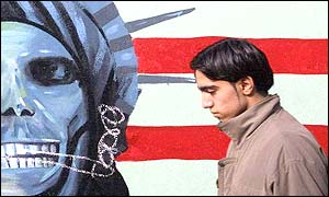 Iranian man and anti-US mural