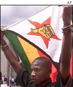 An independent Zimbabwean journalist holds up the Zimbabwean flag during a demonstration outside parliament in central Harare to protest the governments proposed Access to Information and Protection o