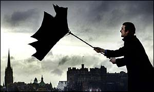 A man tries to control his umbrella in strong winds and heavy rain while walking past Edinburgh Castle