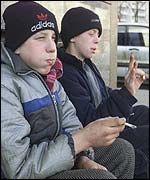 Young homeless boys smoking