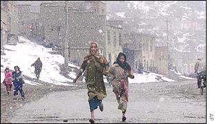 Afghan girls run through Kabul streets as snow flakes fall