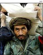 Men carry food sacks in Afghanistan
