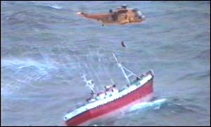 Rescue teams winch the crew to safety