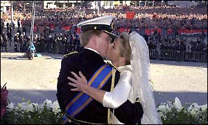Dutch Crown Prince Willem-Alexander kisses Princess Maxima of Argentina on the balcony of the royal palace, backdropped by Dam Square in Amsterdam