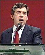 Gordon Brown stands in front of a red background