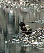 A picture of a child kneeling on a rubbish heap