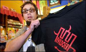 Man holding up t-shirt with Enron depicted as an evildoer