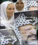 Palestinian woman carrying poster of Yasser Arafat