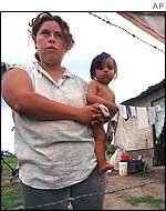 An Argentine woman holds her 10 month-old daughter outside their makeshift house in San Miguel de Tucuman