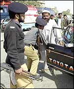 Pakistani police search a car