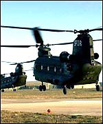 Two Chinook helicopters hover over an airfield