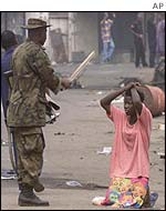 A soldier interrogates a woman in Idi Araba neighbourhood