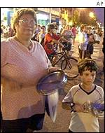 A woman and her son hold pots to bang