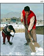 Residents of Kabul clear snow from roof