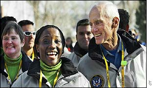 Virgin Islands luger Dinah Browne, left, laughs with chef de mission Larry Heikkila as they enter a team welcoming ceremony at the Olympic Village