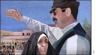 Woman in front of Saddam Hussein poster