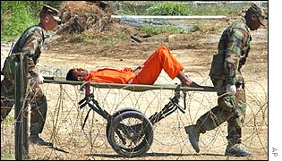 A prisoner strapped to a stretcher is taken for interrogation