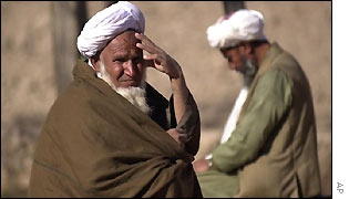 A man looks while another offers prayers near Uruzgan town