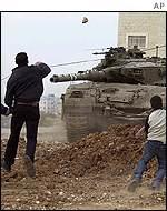 Jóvenes palestinos arrojan piedras a un tanque del ejército                                     de Israel.