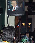 Punters gaze up at President Bush on television