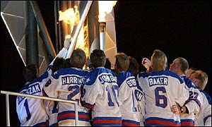 The 1980 Olympic winning ice hockey team light the Olympic flame