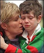 A young fan is comforted by his mother as the Rabbitohs lose an appeal hearing