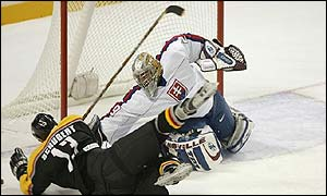 Goaltender Pavol Rybar of Slovakia blocks a shot by Christoph Schubert of Germany
