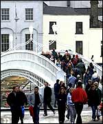 People cross Hapenny Bridge in Dublin
