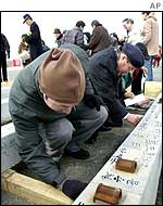 South Koreans at Dorasan station write messages on the railway sleepers