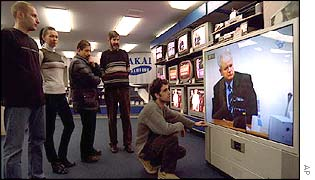 Serbs watch the opening of the trial in a Belgrade TV shop