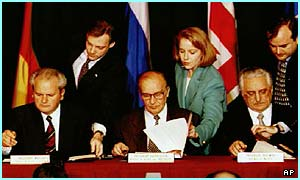 Slobodan Milosevic (left) signs the Bosnia peace agreement