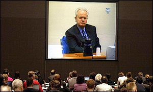 Slobodan Milosevic appears on a giant screen in the pressroom of the Congress building in The Hague