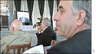 Albanian men watch the trial live in Kosovo's capital Pristina