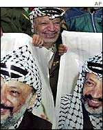 Arafat laughs a photocall including posters of himself