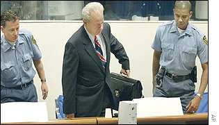 Slobodan Milosevic flanked by guards, sits down in court
