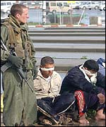 Israeli soldier guards Palestinians at Erez checkpoint