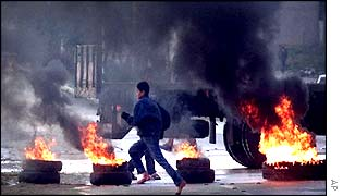 A Palestinian boy runs past burning tires set up as a roadblock against Israeli tanks