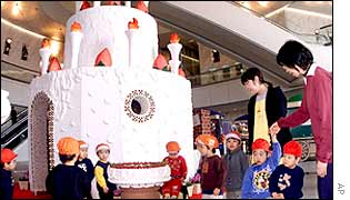 Nursery school children admire a  5-metre-tall cake made of 300kg (661 lbs) sugar, 100kg (220lbs) of eggs, 50kg (110 lbs) of chocolate and 2,000 cookies