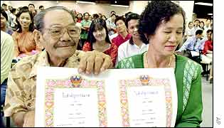 Ting Jaisawas, 81, left, shows marriage certificates after registering with his 58-year-old bride Kadao Takachai, right,