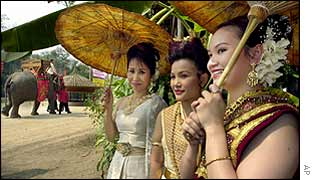 Brides-to-be Patteeya Chaikam, left, Koranun Moonut, centre and On-Achara Kwamphaiboon, right, look on as the grooms ride past on elephants