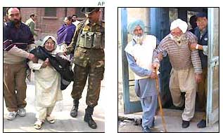 Two elderly voters are helped by officials in Punjab