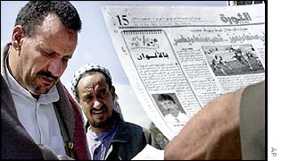 Men read newspapers in the Yemeni capital Sanaa