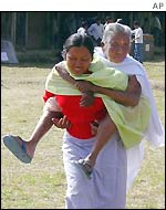 A woman carries her mother to a polling station near Imphal